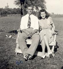 black and white photo of couple sitting on a bench outside